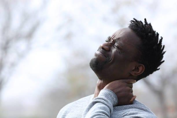 رجل أسود يعاني من آلام في الرقبة ويشكو في الهواء الطلق