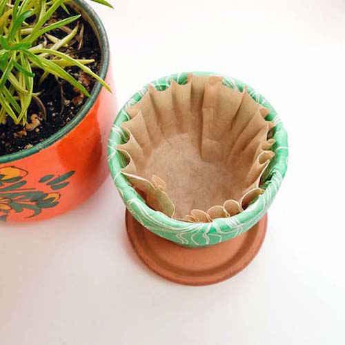 ضع مرشح القهوة في قاع أواني الزهور للاحتفاظ بالماء