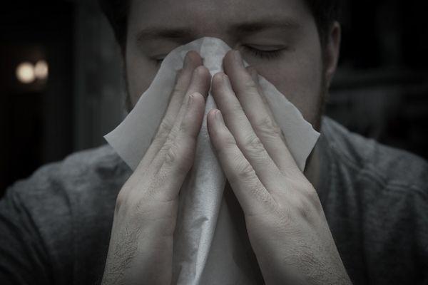 رجل ينفث أنفه بمنديل ورقي بسبب الحساسية