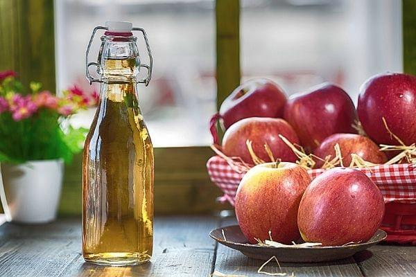 زجاجة من خل التفاح والتفاح الأحمر